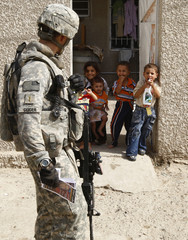 Children smile as they look at a U.S. army soldier on a patrol with the Iraqi police in Baghdad