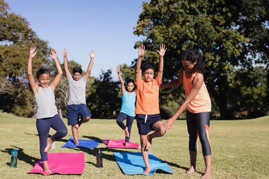 Trainer examining kids practicing yoga