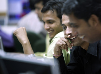 Stockbrokers react while trading at a firm in Mumbai