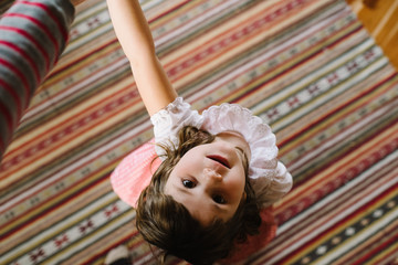 Girl standing on rug and looking up