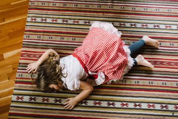Girl lying on rug on floor