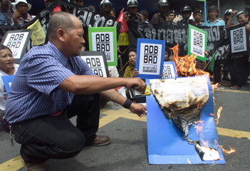 A PROTESTER BURNS AN ASIAN DEVELOPMENT BANK LETTER IN BANGKOK.
