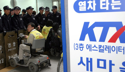 SOUTH KOREAN POLICEMEN BLOCK DISABLED PROTESTERS AT SEOUL RAILWAY STATION.