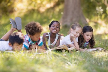 Friends reading book while lying on grassy field