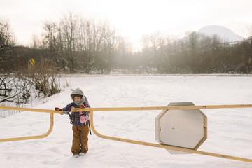 Girl opening gate in snowy field