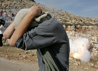 A protester reacts to a stun grenade explosion in Abud