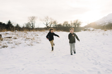Two boys running in snow