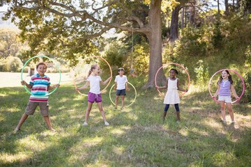Group of cheerful friends playing with hula hoops at campsite