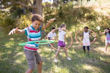 Group of friends enjoying with hula hoops at campsite