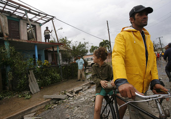 People clean up debris in the aftermath of Hurricane Gustav in Paso Real de San Diego, Cuba