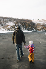 Father holding daughter's hand on beach