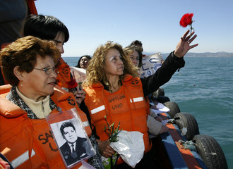 A protestor throws a flower into the sea in memory of those tortured during Pinochet's regimen in ...