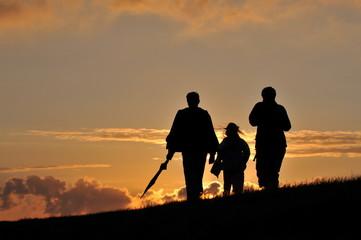 Familie läuft dem Sonnenuntergang entgegen
