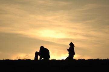 Vater mit Kind auf dem Damm im Sonnenuntergang