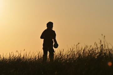 Junge rennt dem Sonnenuntergang entgegen