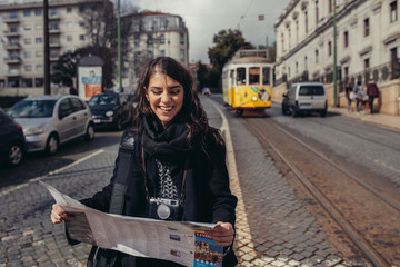 Having fun on Europe trip in capital of Portugal.Traveling to LIsbon.Female turist in front of famous 28 tram holding maps and exploring charming city.Photographer blogger discovering european cities
