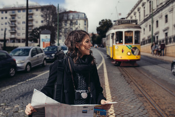 Admiring amazing trip in european metropola.Traveling in Europe.Female turist in front of  famous 28 tram in Lisbon,Portugal.Woman holding maps and exploring charming country