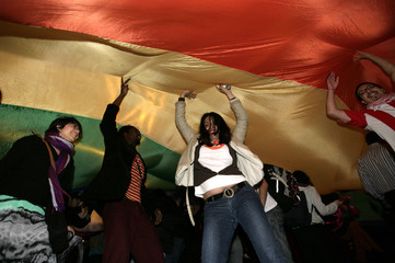 """People dance under a """"diversity"""" flag during a gay pride parade in Montevideo"""