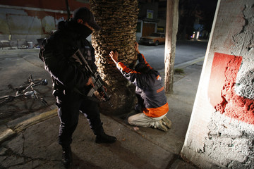 A federal policeman attempts to search a man for drugs and weapons during an anti-narcotics operation in Ecatepec