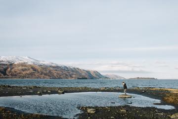 Boy standing on rock in lake
