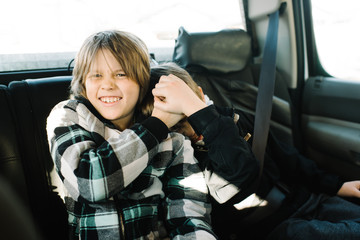 Two brothers play fighting in backseat of car