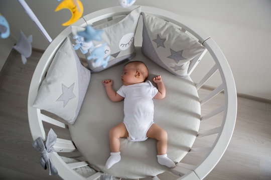 baby boy white t-shirt sleeping in a round bed