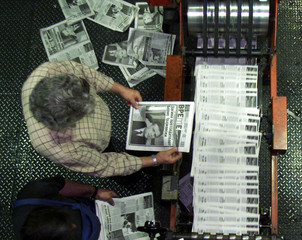 NEWSPRINT WORKER READS EDITION ABOUT DEATH OF MACEDONIAN PRESIDENT.