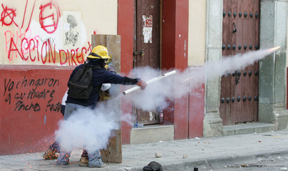 A protester fires fireworks during clashes between demonstrators and federal police near the colonial city centre of Oaxaca