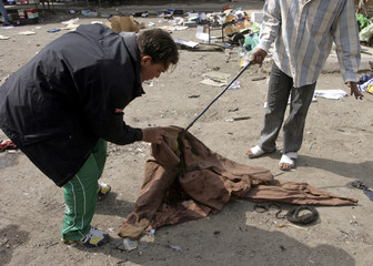 Iraqis look at bloodied cloth at bus station after bomb attack in Baghdad