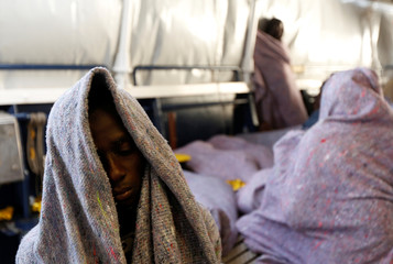 Migrants rest on the Malta-based NGO Migrant Offshore Aid Station (MOAS) ship Phoenix as it makes its way towards Italy after rescue operations off the coast of Libya