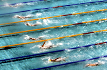 Swimmers compete in the first semi-final of Men's 100 metres backstroke at the Athens Olympic aquati..