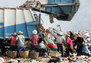 Garbage collectors look for waste to recycle at a garbage dump site in Sanya