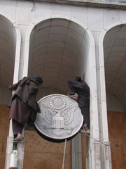 TWO PROTESTORS TRY TO REMOVE THE EMBLEM OF AMERICAN EMBASSY IN THEAFGHAN CAPITAL.