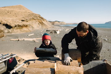 Father and son stacking logs on beach