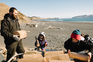 Father and children stacking logs on beach