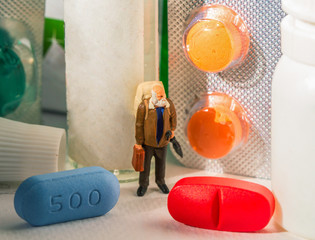 Bright pills and Elder man Figurine. Pharmacy for elder people concept.