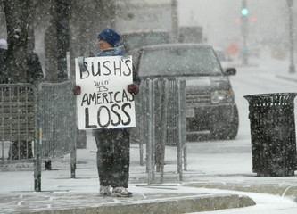 A lone demonstrator holds a sign protesting the election of U.S. President George W. Bush near the ...