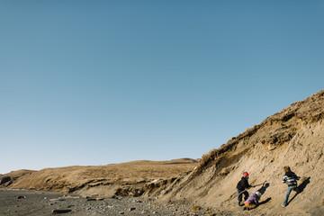 Children playing on beach cliff