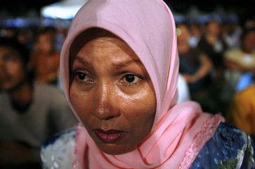 Supporter of Malaysia's politician Anwar Ibrahim holds back tears as she recites a prayer during a rally marking the end of a ban that barred him from seeking public office, in Kuala Lumpur