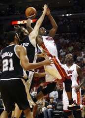 Miami Heat Wade is defended by San Antonio Spurs Duncan during NBA basketball game in Miami