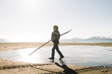 Boy walking with long stick on beach