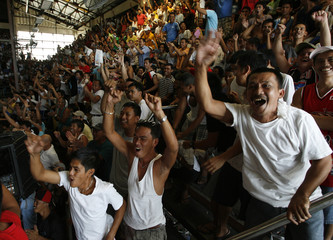 Supporters of Filipino boxer Manny Pacquiao cheer while watching a live telecast in a Manila gymnasium of Pacquiao's WBO welterweight title fight with Puerto Rican Miguel Cotto