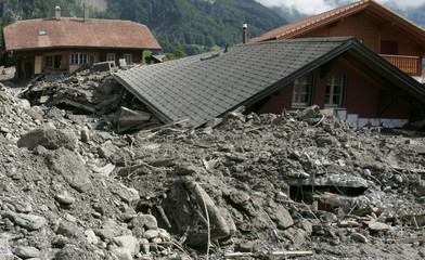 Picture shows houses damaged by mud and debris caused by recent floods in the village of Brienz.