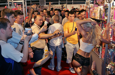 Spectators take pictures as an actress performs a striptease at the Erotic Fair in Belgrade.