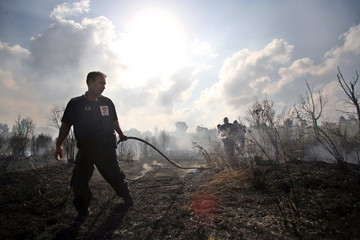 Israeli firefighter extinguishes fire which was caused by rocket falling near the northern town of Nahariya
