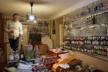 Yuri Kreshkov arranges some the 3,000 bottles he has collected over the past 20 years displayed in his two-room apartment in Kiev