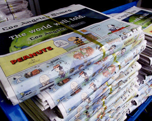 """Stacks of the Sunday edition of the Los Angeles Times, with the final Sunday """"Peanuts"""" comic strip b.."""