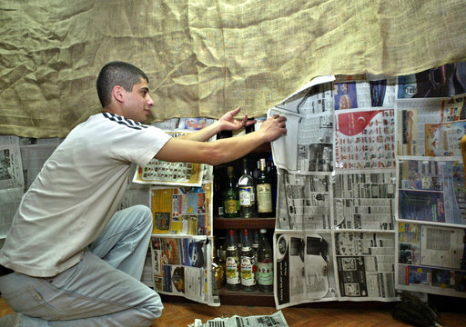 LIQUOR WORKER COVERS SHELVES OF ALCOHOLIC DRINKS WITH NEWSPAPERS DURINGRAMADAN.