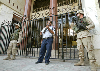 TWO U.S. SOLDIERS AND AN IRAQI POLICEMAN IN GUARD THE MAIN ENTRANCE OFWARKAA INVESTMENT BANK IN THE ...