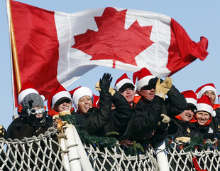 Sailors wearing Santa hats wave from the deck of the HMCS Toronto as it arrives in Halifax